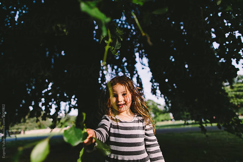 Little girl playing with the tree branch by Evgenij Yulkin for Stocksy United