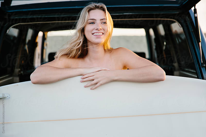 Surfer girl smiling with surfboard  by Curtis Kim for Stocksy United