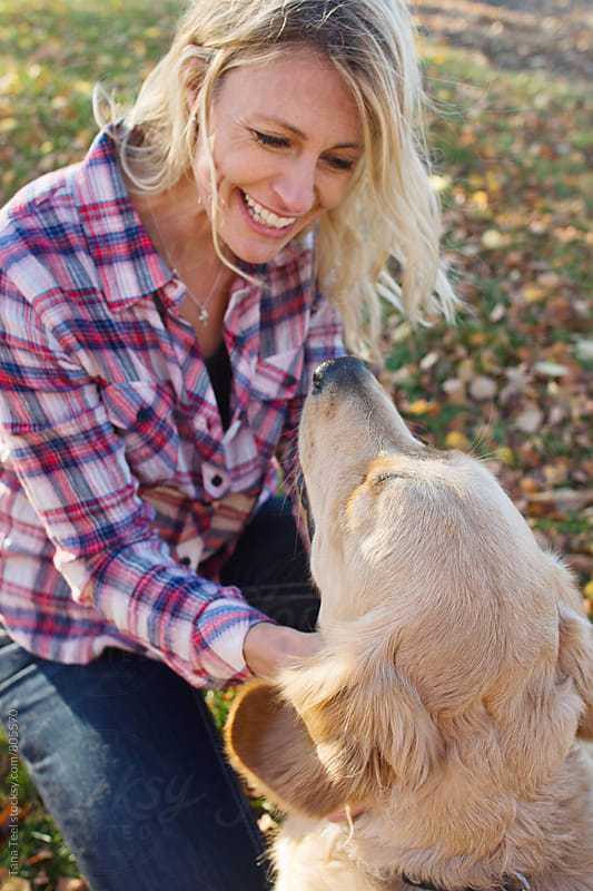 smiling woman pets her dog by Tana Teel for Stocksy United