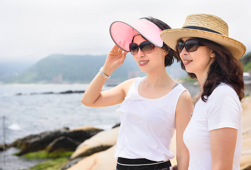 Two women in sunhat looking away by Lawren Lu for Stocksy United