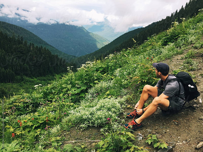 Male Hiker Stopping to Tie Shoe on an Alpine Meadow Trail in Washington by michelle edmonds for Stocksy United