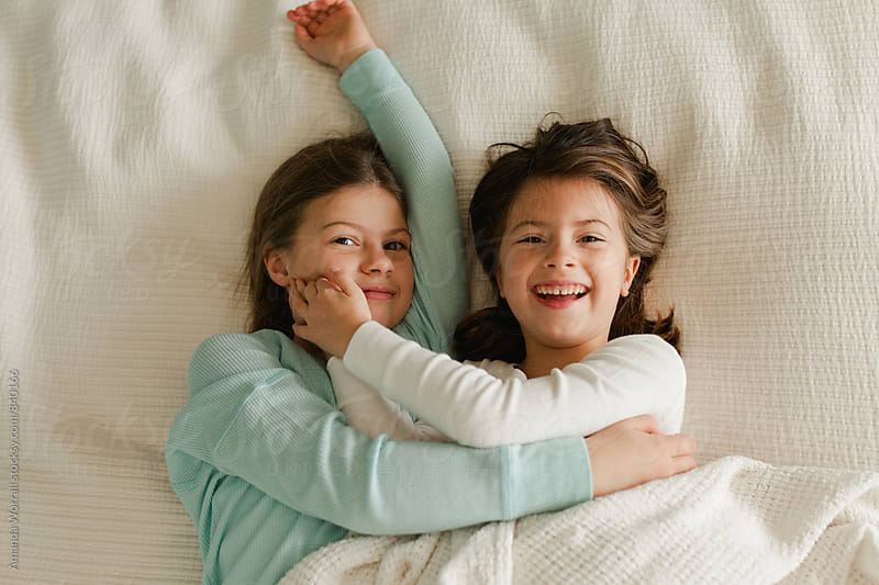 Happy sisters cuddling in bed by Amanda Worrall for Stocksy United