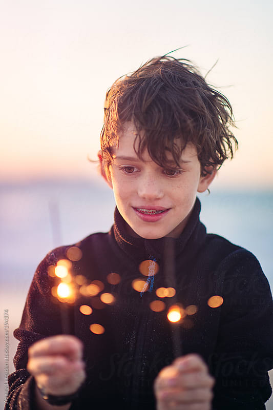 Boy holding sparklers at sunset by Angela Lumsden for Stocksy United