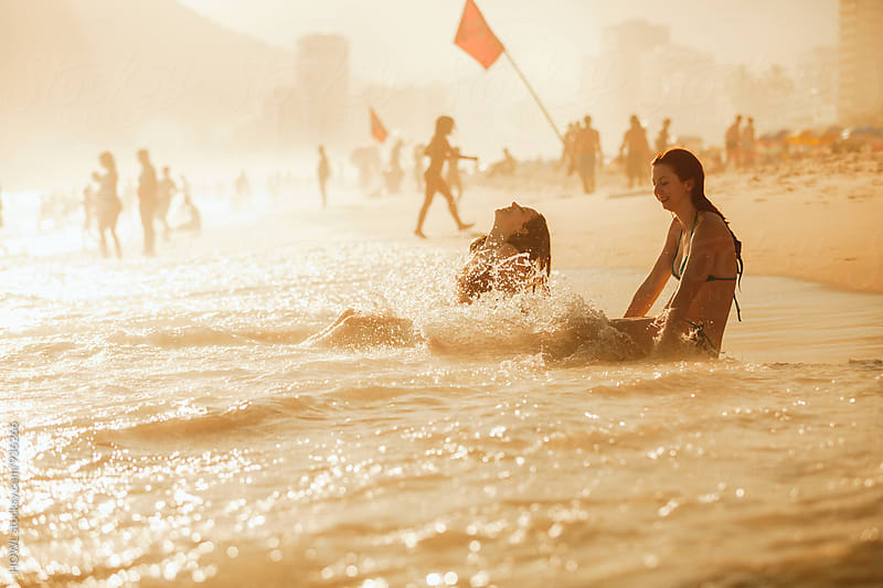 Two friends playing in the crashing waves of Brazil's famous Ipanema Beach by HOWL for Stocksy United