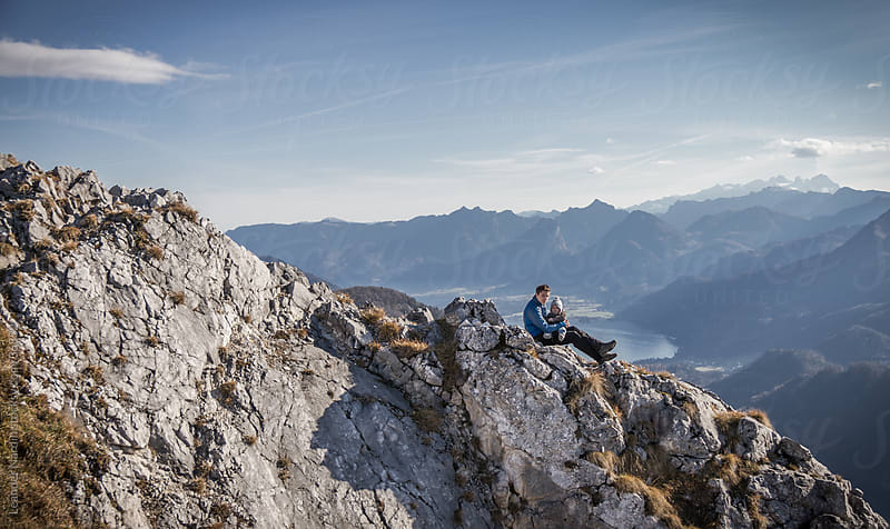 father and son on top of a mountain by Leander Nardin for Stocksy United