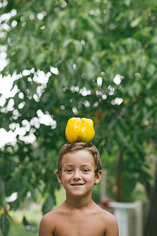 Child carrying yellow pepper on his head by Dejan Ristovski for Stocksy United