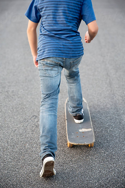Young kid riding his skateboard on the street by Curtis Kim for Stocksy United