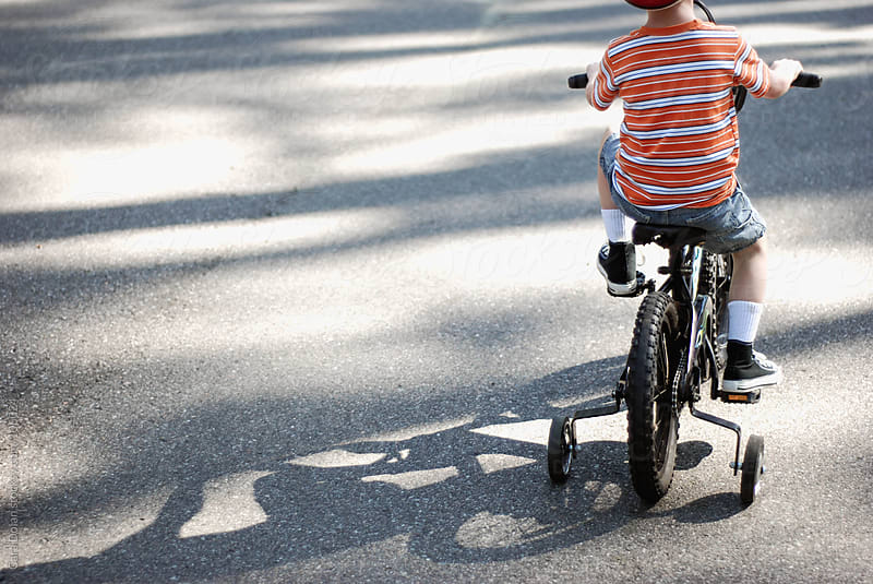 Boy rides a bike with training wheels attached by Cara Dolan for Stocksy United