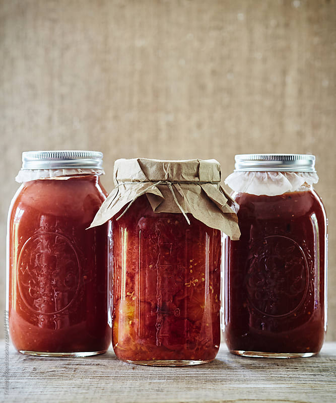 Canned preserved tomato sauce in three mason jars by Trinette Reed for Stocksy United