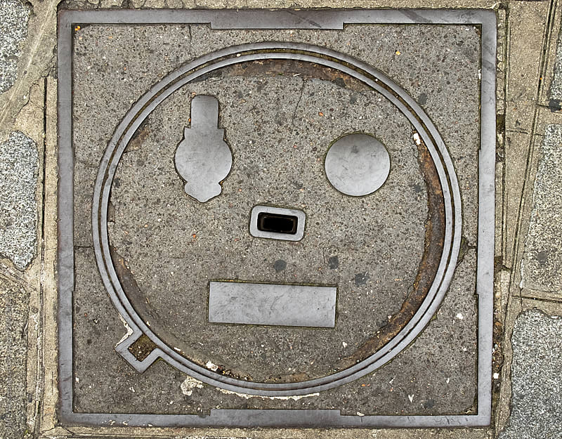 Happy Face Manhole Cover  by Jeff Wasserman for Stocksy United