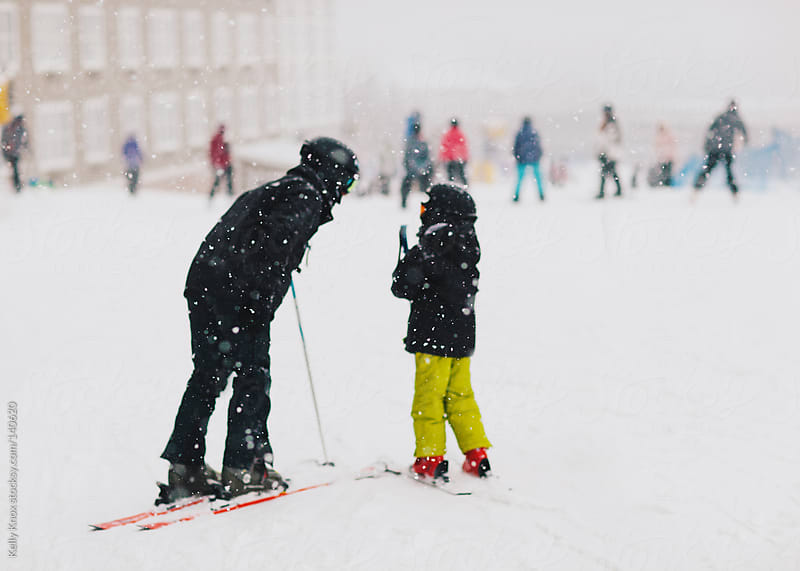 father teaches child to ski by Kelly Knox for Stocksy United