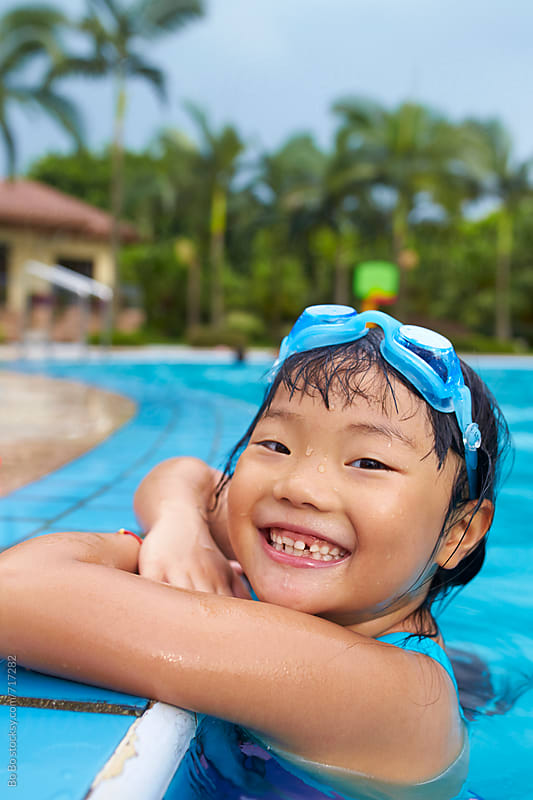 happy little asian girl in swimming pool by Bo Bo for Stocksy United
