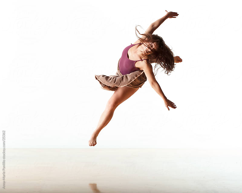 Female dancer leaping with arms outstretched by Anna-Marie Panlilio for Stocksy United