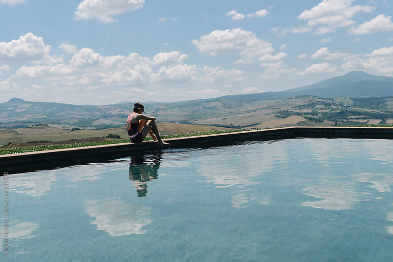Girl dipping her toe into a still swimming pool in Tuscany, Italy. by Kirstin Mckee for Stocksy United