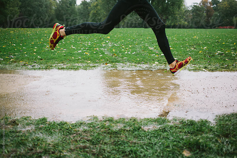 Photo of legs of a runner  in the rain jumping over a puddle by Ivo de Bruijn for Stocksy United