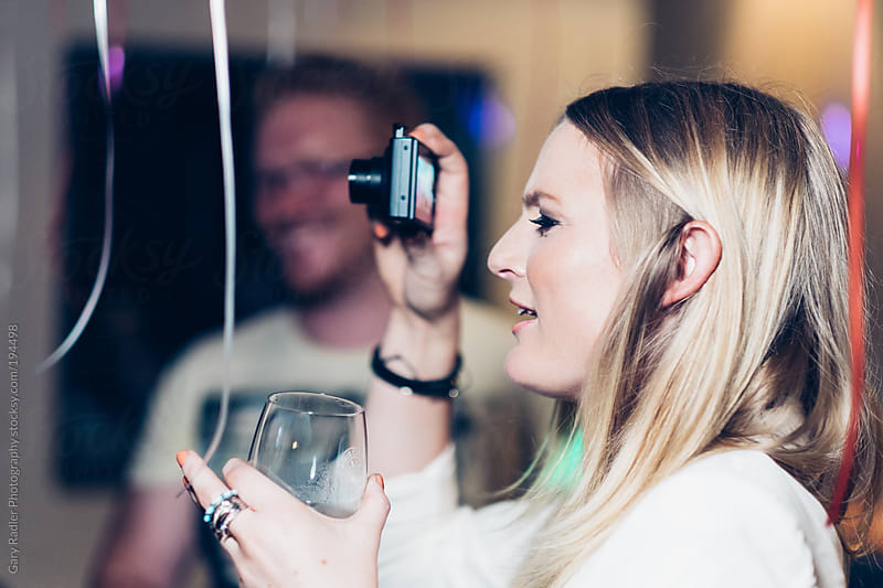 Young Woman taking a Photo at a Party by Gary Radler Photography for Stocksy United