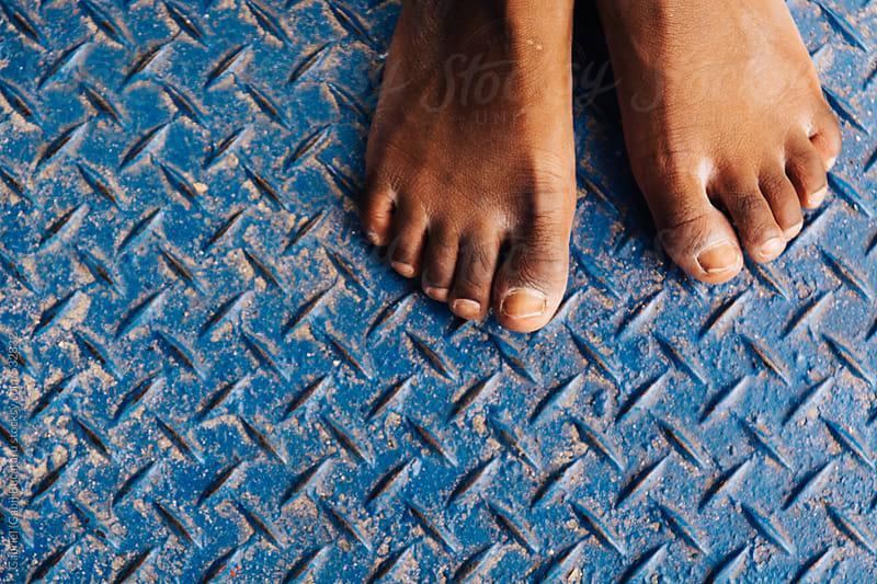 Feet of an African American child on a blue metallic floor by Gabriel (Gabi) Bucataru for Stocksy United