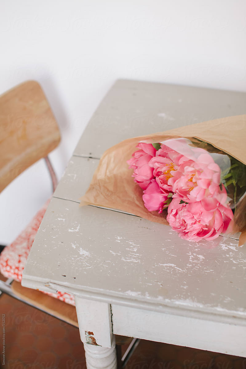 Table With Bright Pink Peonies Wrapped In Brown Paper Stocksy United