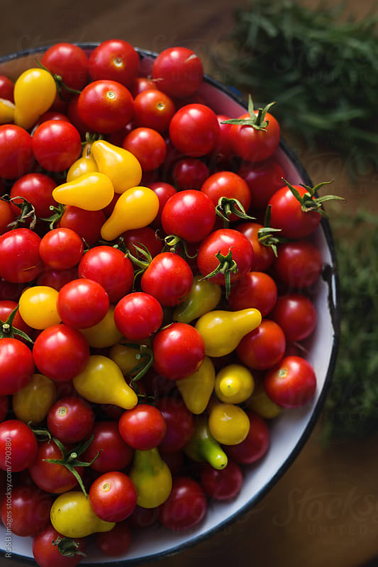 Fresh red and yellow cherry tomatoes in a pot by RG&B Images for Stocksy United