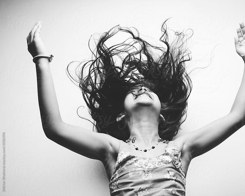 A young happy child throwing her hair. by Shikhar Bhattarai for Stocksy United