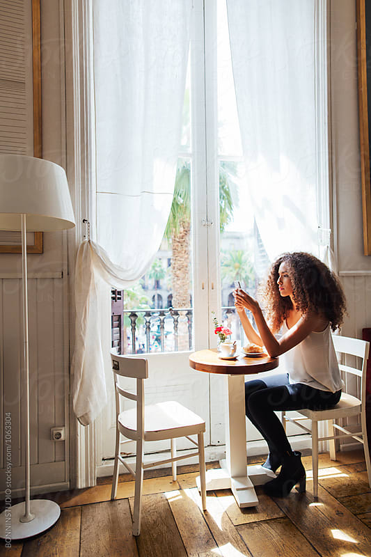 Side view of a businesswoman using her phone whilst having breakfast at coffee bar.  by BONNINSTUDIO for Stocksy United