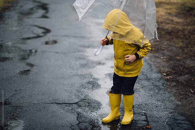 little boy in yellow raincoat and yellow boots walking with an umbrella. by Léa Jones for Stocksy United