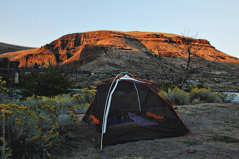 Tent set up alongside river and train tracks by Tari Gunstone for Stocksy United