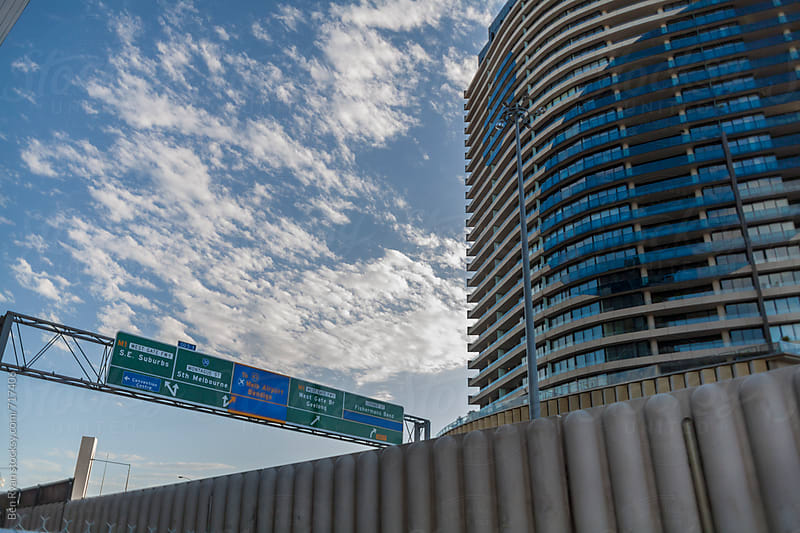 Freeway signs alongside apartment tower with high cloud background by Ben Ryan for Stocksy United