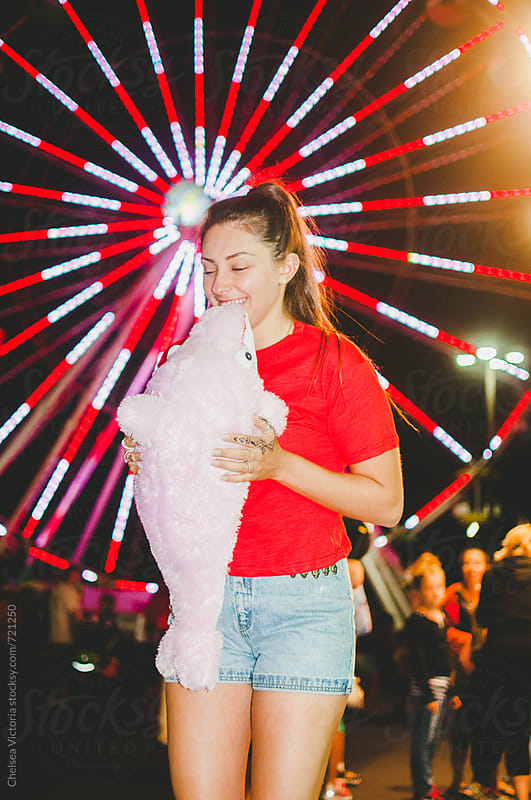A young woman standing in front of a ferris wheel holding a stuffed animal by Chelsea Victoria for Stocksy United