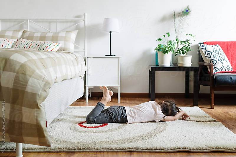 Adorable little girl lying on mat by MaaHoo Studio for Stocksy United