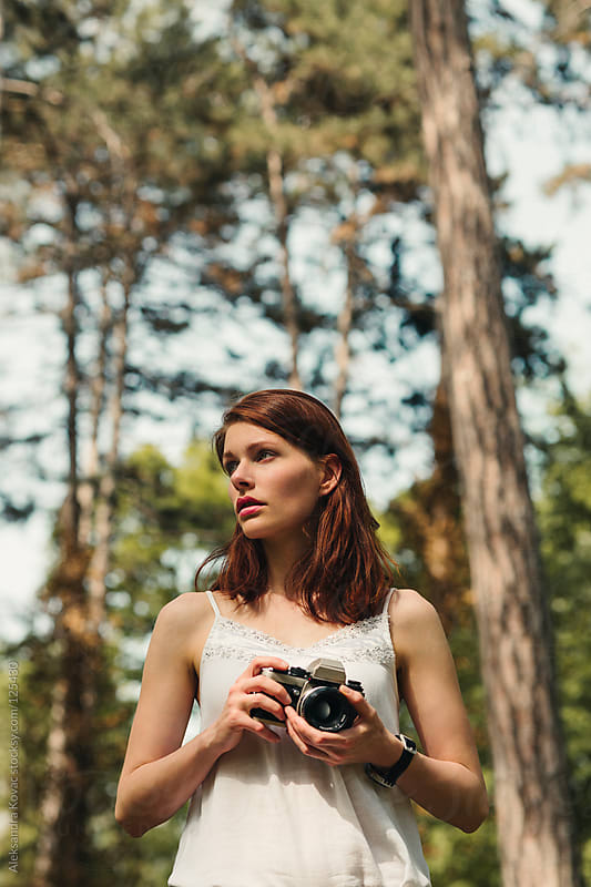Woman with a camera in the woods by Aleksandra Kovac for Stocksy United