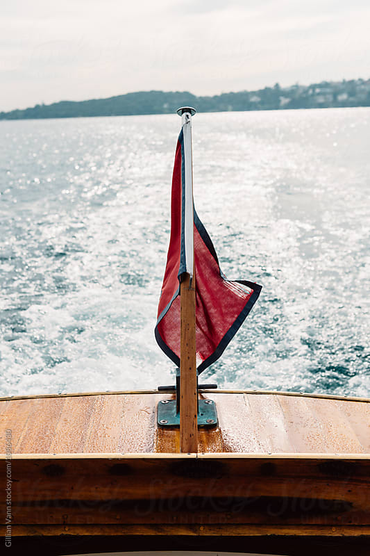 flag on the back of a timber yacht by Gillian Vann for Stocksy United