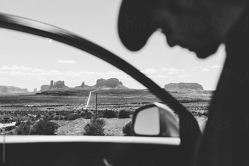 Man on the road in Monument Valley by michela ravasio for Stocksy United