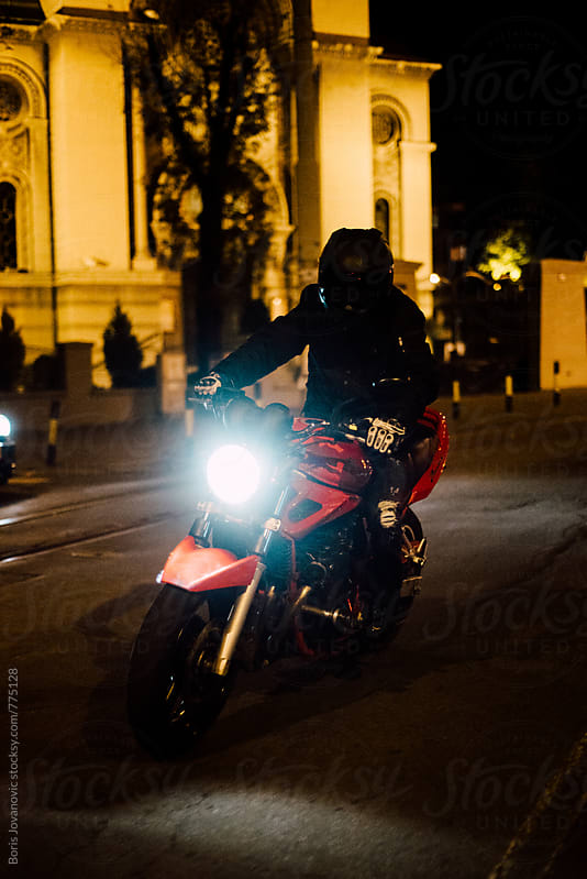 Biker riding a motorcycle on the street at night by Boris Jovanovic for Stocksy United