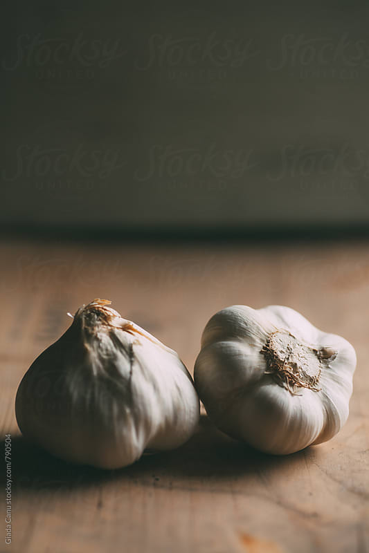 Garlic on wooden table by Giada Canu for Stocksy United
