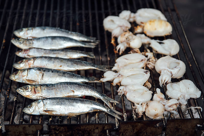 Food: Sardines and Polpo on a barbecue grill by Ina Peters for Stocksy United