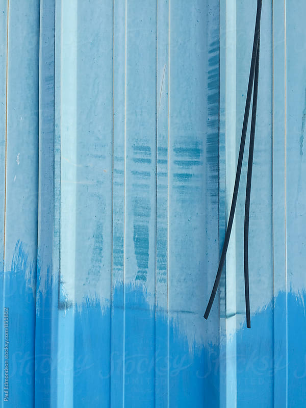 Close up of blue paint covering graffiti on metal wall by Paul Edmondson for Stocksy United
