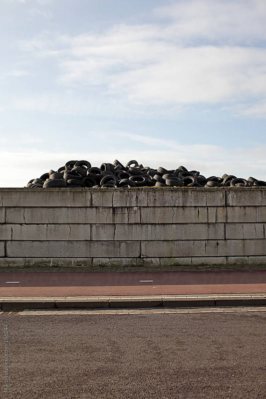 Pile of car tires behind a wall by Marcel for Stocksy United