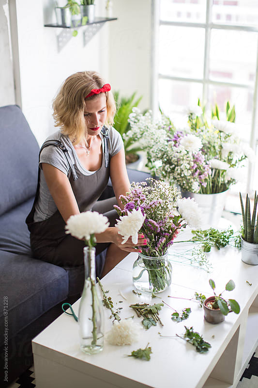 Beautiful woman arranging flowers picked from her garden at home  by Jovo Jovanovic for Stocksy United