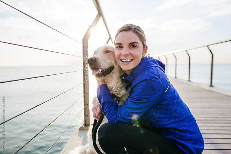 Portrait of a runner woman and her dog at sunrise. by BONNINSTUDIO for Stocksy United