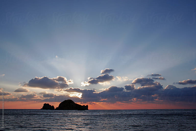 Twighlight rays above the silhouette of sea rocks by Ferenc Boros for Stocksy United