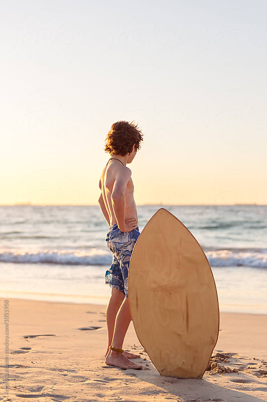 Boy standing with a skim board and looking at the ocean by Angela Lumsden for Stocksy United