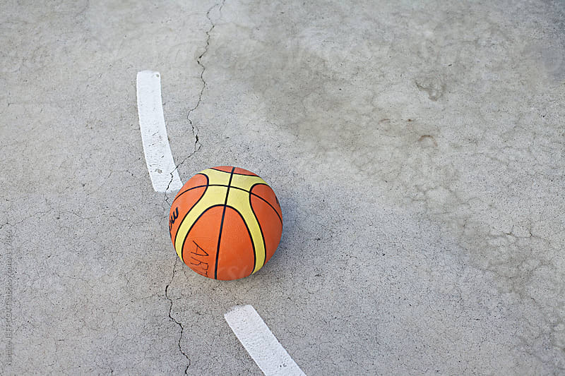 basketball sitting on outdoor court by Natalie JEFFCOTT for Stocksy United