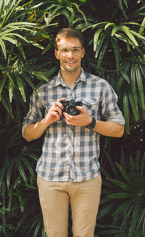 Man holding a vintage camera and smiling.  by Jovo Jovanovic for Stocksy United