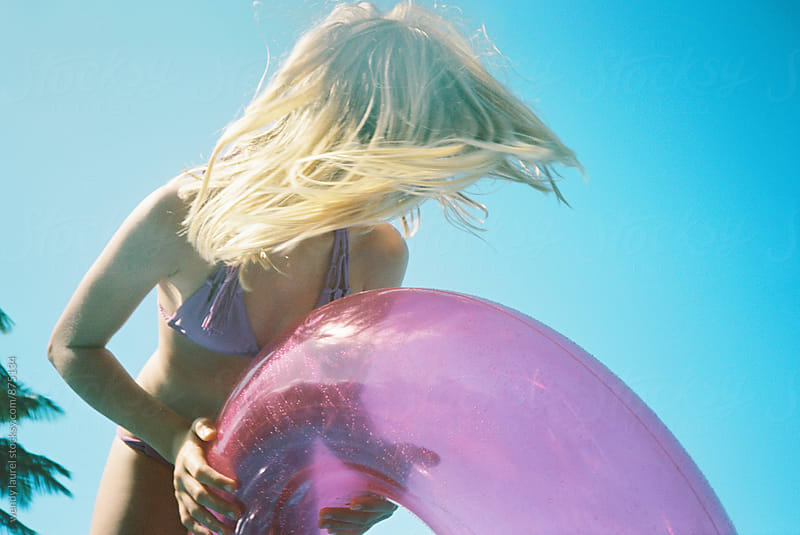 blonde girl in bikini with pink floatie tossing hair in front of blue sky by wendy laurel for Stocksy United