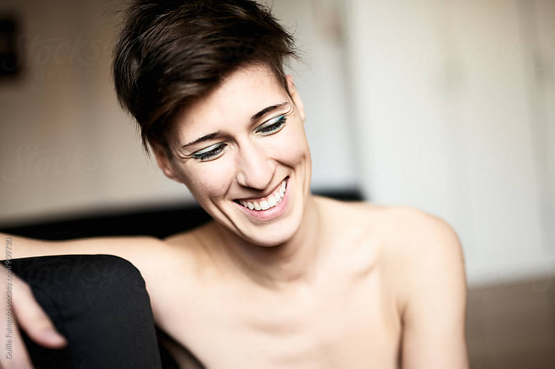 Short haired smiling woman looking down by Guille Faingold for Stocksy United