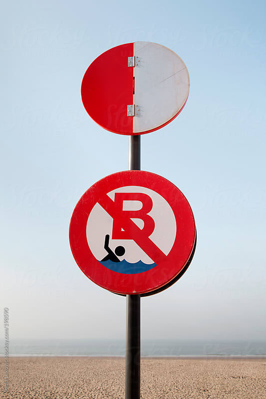 forbidden swimming sign on a beach by Sonja Lekovic for Stocksy United