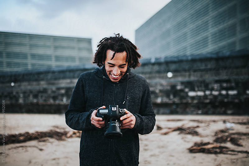 young man laughting at his camera by Thais Ramos Varela for Stocksy United