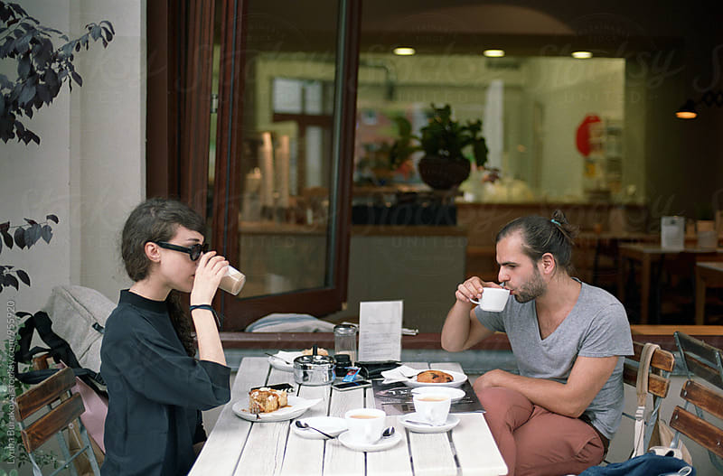 Young man and woman having breakfast outdoors by Lyuba Burakova for Stocksy United