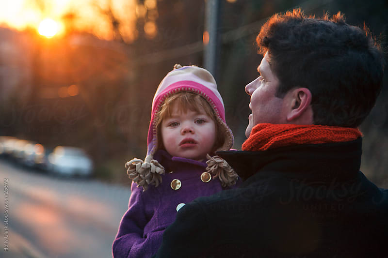 Father carries daughter at sunset in the city by Holly Clark for Stocksy United